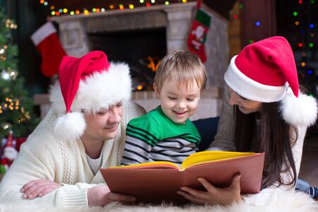Portrait of happy family reading book on Christmas evening photo