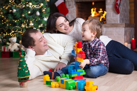 Kid boy and his parents playing with block toys under the christmas tree photo