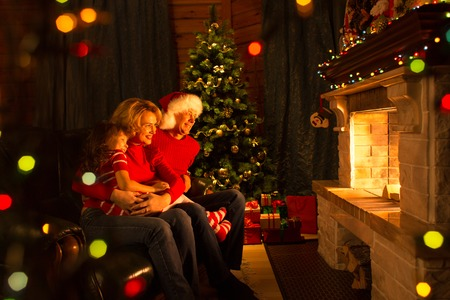 fireplace family: Family looking at fireplace in Christmas decorated house interior Stock Photo
