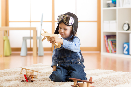 happy child boy plays with toys airplane and dreams of becoming a pilot