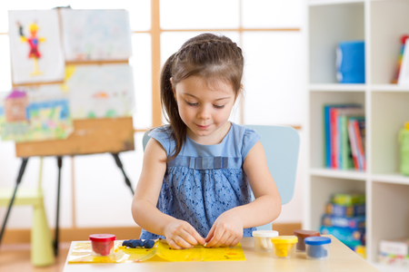 sculpt: Kid girl plays plasticine or dough at home