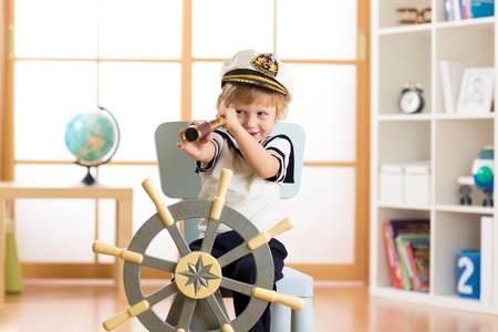 sailor hat: Child pretend to be sailor. Little boy looking through spy glass playing at home. Stock Photo