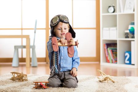 bambino che finge di essere aviatore pilota. Bambino che gioca con gli aeroplani giocattolo in casa. Viaggi e sogno concetto