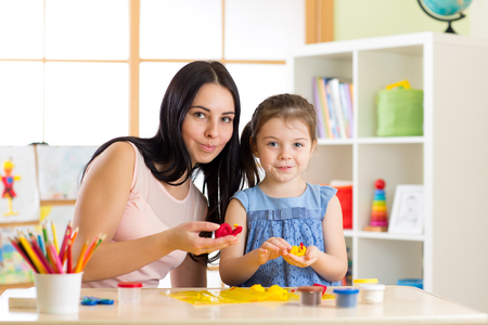 day care: Teacher and kid girl learn mold from plasticine in kindergarten