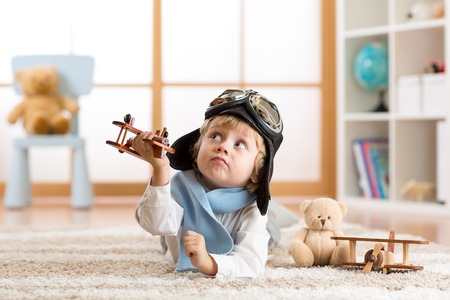 Child boy toddler playing with toy airplane and dreaming of becoming a pilot Foto de archivo