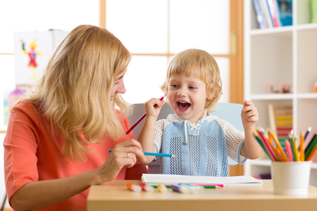 teaching crayons: Happy family mother and kid son together paint. Woman helps child boy. Stock Photo