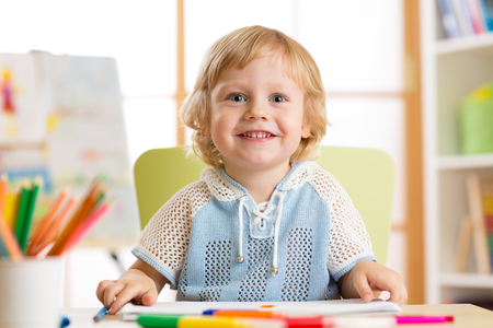 cute child little boy drawing with felt-tip pen in kindergarten classroom Stock Photo