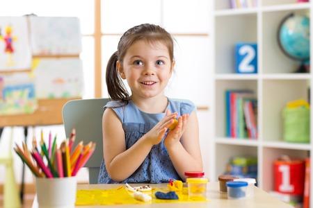 어린이 창의력. 아이 클레이에서 sculpts. 테이블에 plasticine에서 귀여운 소녀 금형