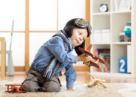 Children dreams concept. Adorable little boy playing with wooden airplane