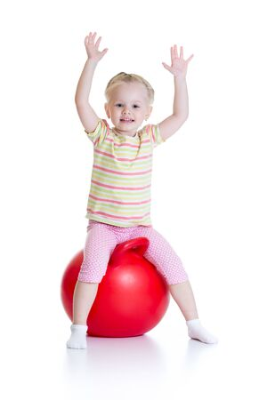 exhilarated: Smiling little girl jumping on a big ball isolated white background