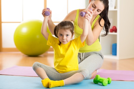 Woman helps little child doing fitness exercises with dumbbells in gym Stock Photo