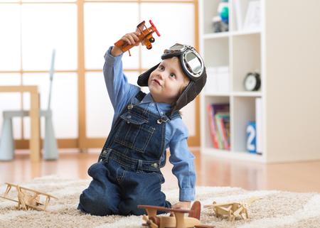bambino felice bambino ragazzo giocando con aeroplano giocattolo e sogna di diventare un pilota