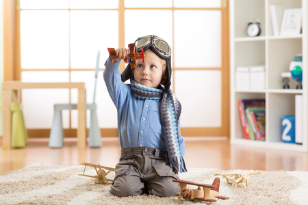 wooden toy: Happy child boy plays with wooden toy airplanes on floor in nursery room Stock Photo
