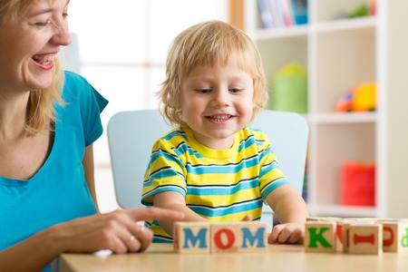 teaches: Mother teaches son child to read letters and words playing with cubes