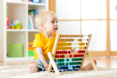 Preschooler baby learns to count. Cute child playing with abacus toy. Little boy having fun indoors at kindergarten, playschool, home or daycare centre. Educational concept for preschool kids.