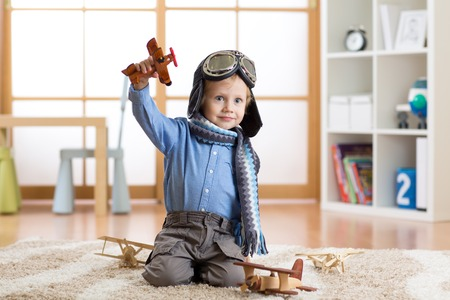 wooden toy: Child pretending to be aviator. Kid playing with toy airplanes at home