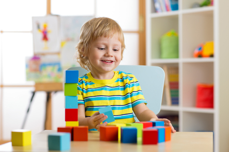 kid boy playing with block toys in day care center Stock Photo