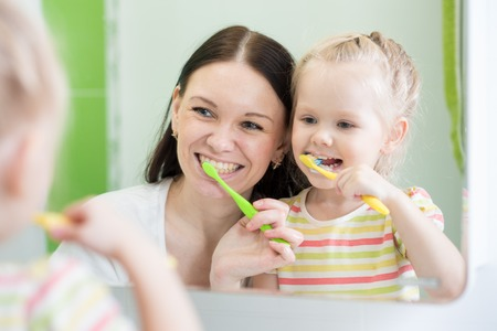Mother And Child Daughter Brushing Teeth Together Stock Photo