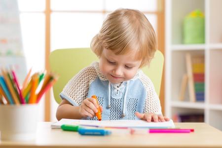 preschooler: Cute child boy is drawing with felt-tip pen in preschool