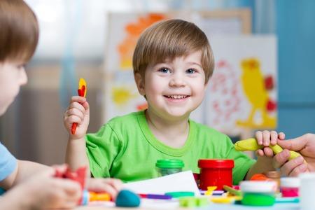 Enfants créativité. Les enfants de sculpture de l'argile. Mignon petits garçons moule de plasticine sur la table à la maternelle Banque d'images - 70527657