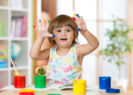 cute cheerful kid girl showing her fingers painted in bright colors Stock Photo
