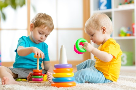 Children playing together. Toddler kid and baby play with blocks. Educational toys for preschool kindergarten child. Friends little boys build pyramid at home or daycare.