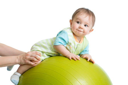 limbering: Close-up portrait of smiling baby on fitness ball. Exercise and massage, baby health conception