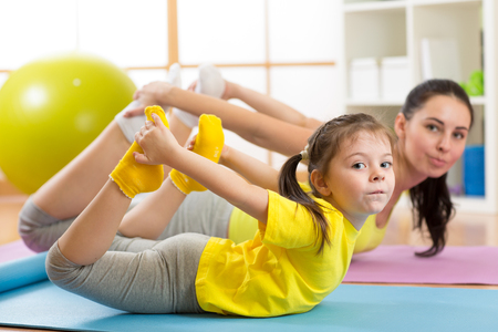 Mother and child doing yoga exercises on rug at home. Stock Photo - 71018438