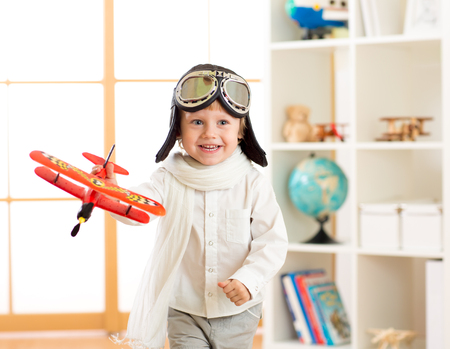 happy child boy play in airplane indoors