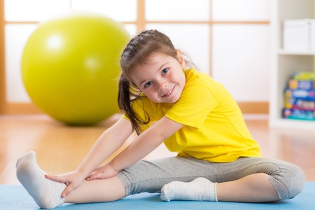 Kid doing fitness exercises Stock Photo