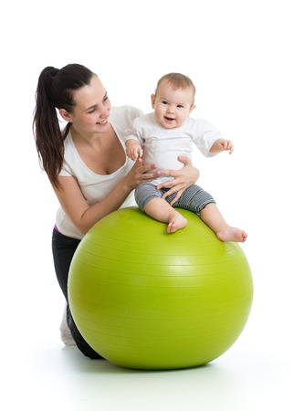 young mother and her baby infant doing yoga exercises on gymnastic ball isolated over white photo