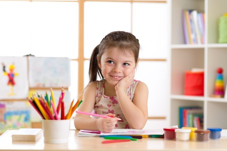 Smiling kid girl drawing with color pencils in day care center