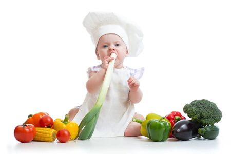 broccolli: Little girl dressed in white chef hat and apron eats fresh onion. Child with vegetables: eggplant, popcorn, broccolli, peppers, zucchini, tomatoes