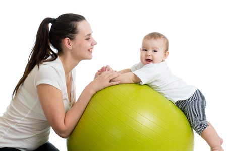 Happy mother and baby making healthy gymnastics on fit ball photo