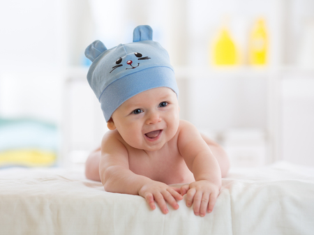 teething: Portrait of a cute 5 months baby lying down on bed Stock Photo