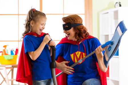 dressed: Happy woman and kid prepare for room cleaning. Mother and her child girl playing together. Family in Superhero costumes. Stock Photo