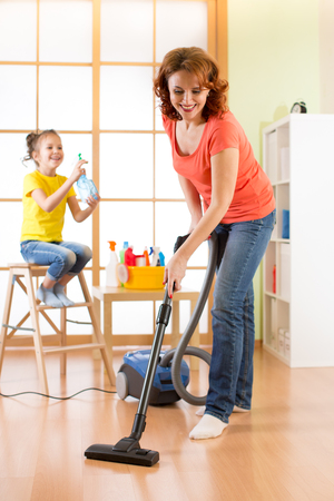 hoover: Portrait of smiling middle-aged woman vacuuming at home
