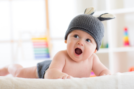 Smiling cute baby child in rabbit costume lying on bed in nursery