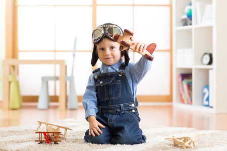 Child pretending to be aviator. Kid playing with toy airplanes at home
