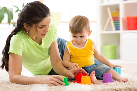 child and his mother playing together with toys