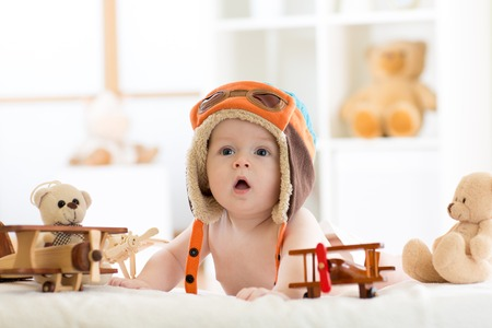 baby toys: Funny baby boy weared pilot hat with wooden airplane and teddy bear toys Stock Photo