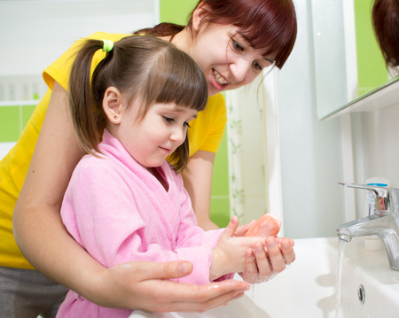 concern: Mother and kid daughter washing their hands in the bathroom. Care and concern for children.