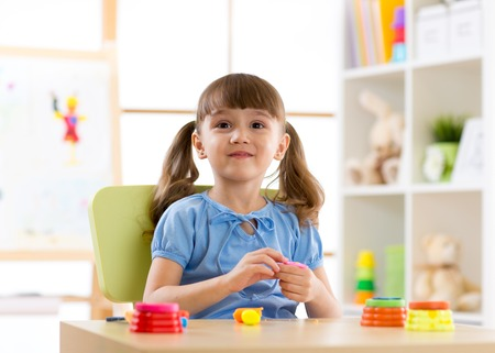 Kid girl playing with plasticine at home Stock Photo