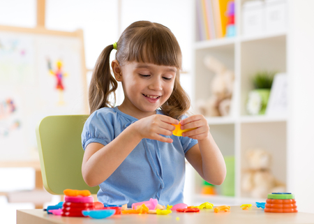 Little kid girl is playing with plasticine while sitting at table