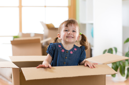 Laughing little girl sitting in cardboard boxe in her new home
