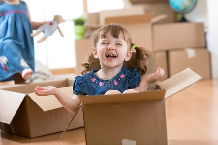 Happy kid inside box at new home after moving