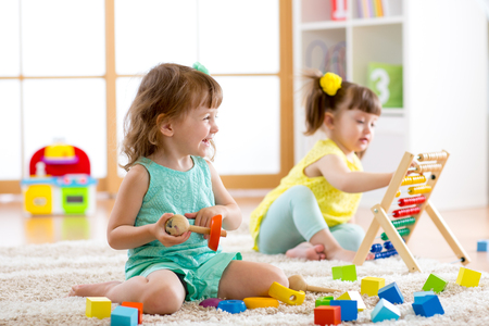 Little kids girls playing with abacus and constructor toys in kindergarten, playschool or daycare center