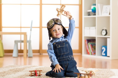 happy kid toddler playing with toy airplane and dreaming of becoming a pilot Stock Photo