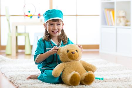 집에서 봉제 장난감으로 의사를 재생 귀여운 아이 소녀 스톡 콘텐츠