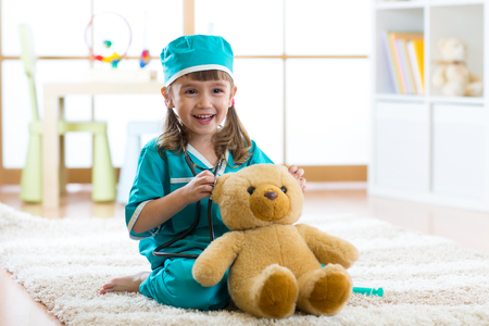 Cute kid girl playing doctor with plush toy at home Standard-Bild